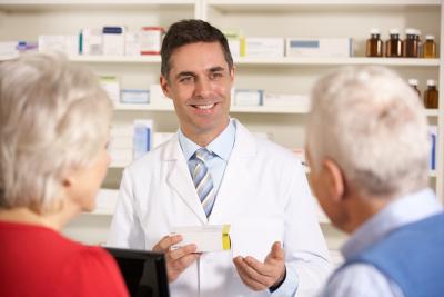 pharmacist with senior couple in pharmacy